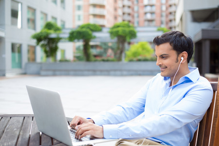 indian boy: Closeup portrait, young handsome man in blue shirt typing away, listening to headphones, browsing digital computer laptop, isolated background of sunny outdoor, green trees, office background Stock Photo