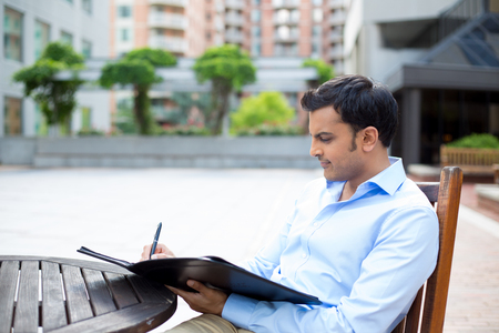 Closeup portrait, young business man deep in concentration, writing notes, sitting on wooden chair at table, isolated city background with buildings photo
