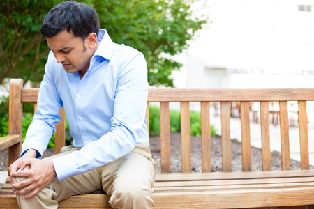 dolor de rodilla: Primer retrato, hombre joven y guapo con camisa azul, pantalones de color caqui marrón, sentado en el banco de madera en el dolor de rodilla grave, árboles aislados fondo exterior. Emoción humana Negativo