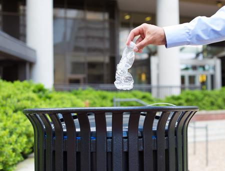 reciclar: Primer retrato, pl�stico mano de lanzar la botella de agua vac�a en contenedor de reciclaje, aislado edificio y los �rboles de fondo