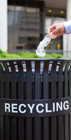cesto basura: Primer retrato, plástico mano de lanzar la botella de agua vacía en contenedor de reciclaje, aislado edificio y los árboles de fondo
