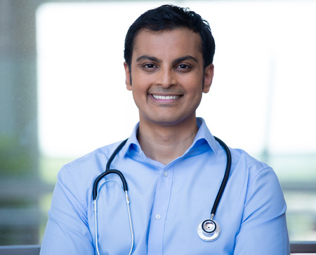 Closeup portrait of friendly, smiling confident male doctor, healthcare professional with stethoscope around neck, arms crossed.  photo