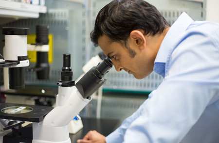 research worker: Closeup portrait, young scientist looking into microscope. Isolated lab background. Research and development. Stock Photo