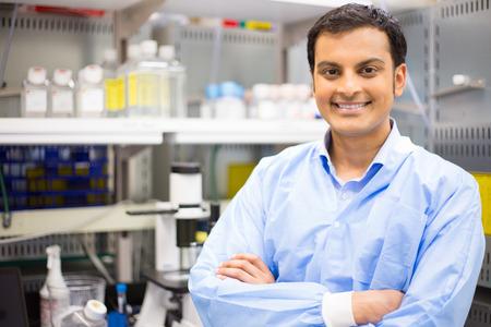 Close-up portret, jonge lachende wetenschapper in blauwe jas lab staan door de microscoop. Geïsoleerde lab achtergrond. Onderzoek en ontwikkeling.