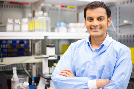 trial: Closeup portrait, young smiling scientist in blue lab coat standing by microscope. Isolated lab background. Research and development.