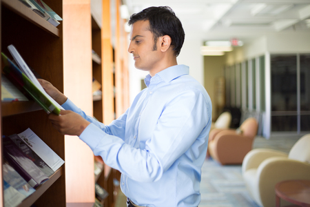 periodicals: Closeup portrait, young business man in blue shirt reading, perusing books, magazines, and periodicals at library