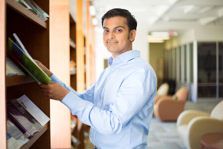Closeup portrait, young business man in blue shirt reading, perusing books, magazines, and periodicals at library photo
