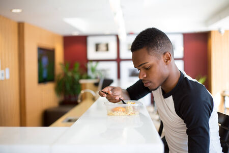 black teens: Closeup portrait young handsome man eating noodles, sitting at white table, isolated luxurious, urban indoor background Stock Photo