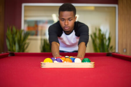 Closeup portrait, young man hanging out, playing billiards at red pool table, isolated indoors background photo