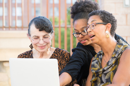 exciting: Closeup portrait, multigenerational family looking at something exciting on laptop, isolated outdoors background