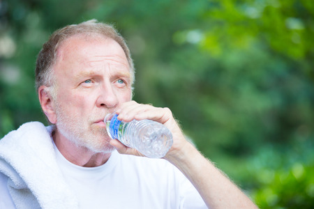 man drinking water: Closeup portrait, thirsty senior mature man drinking water outside, isolated green tree foliage background