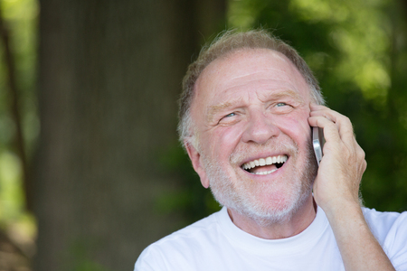 Closeup portrait, older, happy ecstatic man with wide open mouth talking on cell phone, isolated outdoors background photo