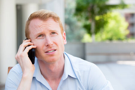Closeup portrait, worried young man in blue shirt talking on phone to someone, looking up, isolated outdoors background