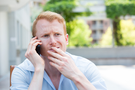 befuddled: Closeup portrait, young man perplexed, baffled, befuddled, bewildered by someone talking on his mobile phone, isolated outdoors background