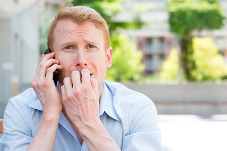 afraid man: Closeup portrait, young man biting finger nails, worried about something he hears on phone, isolated outdoors background