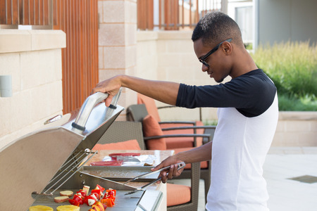tantalizing: Closeup portrait, handsome young guy with big glasses barbecuing yummy food, isolated outside background