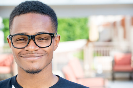 Closeup headshot portrait of fine young man with big glasses, undergrad student, smiling, isolated on outside outdoors background.
