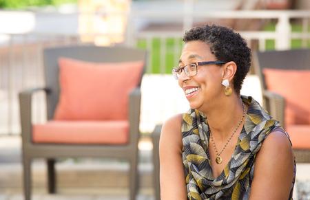 lenguaje corporal: Primer retrato, mujer madura con gafas sentado y sonriente, fondo al aire libre aislado con muebles de jardín