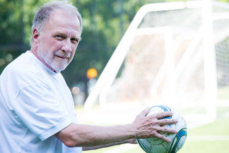 Closeup portrait, senior mature man in white shirt holding soccer ball up, ready to play, isolated background of goal and green football field outdoors