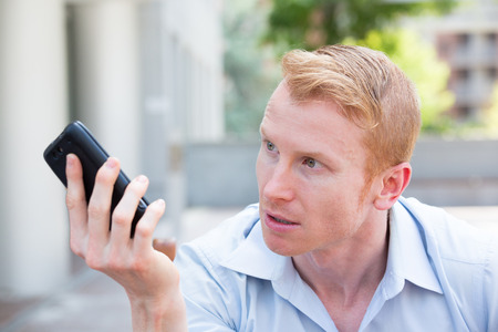 Closeup portrait, annoyed young man, pissed off by what he heard or saw on his cell phone, isolated outdoors background