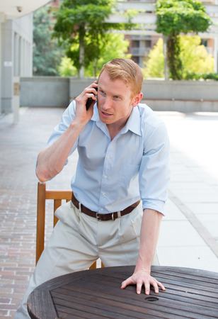 miffed: Closeup portrait, angry young man in blue shirt, annoyed by what he hears on cell phone, standing up with hand on table, isolated outdoors background Stock Photo