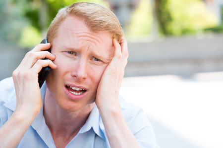 worried man: Closeup portrait, worried young man in blue shirt talking on phone to someone, looking gloomy, isolated outdoors outside background
