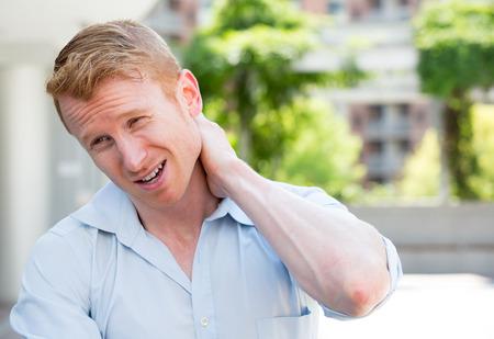 crick: Ritratto del primo piano, giovane uomo in camicia blu con dolore al collo spinale vertebre toraciche dopo lunghe ore di lavoro e di studio, isolato all'aperto all'esterno sfondo. Mancanza di supporto ergonomico