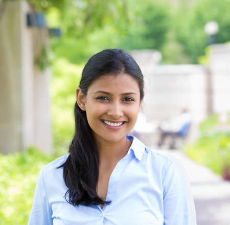 indian people: Closeup headshot portrait, young beautiful business woman in blue shirt smiling isolated on nature background with trees. Positive human emotion facial expression Stock Photo