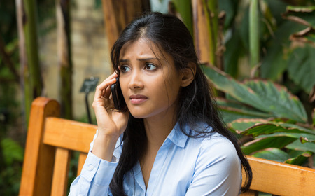 Closeup portrait, sad, depressed, unhappy worried young woman talking on phone, sitting on bench, isolated trees background. Negative human emotions, facial expressions, feelings, reaction. Bad news. Stock Photo