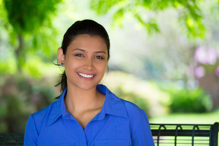 indian professional: Closeup headshot portrait young beautiful happy business woman, sitting on bench, isolated green trees, nature background. Positive human emotion facial expression feelings