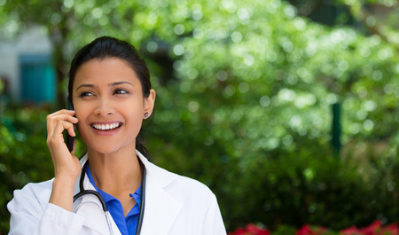 Closeup portrait, friendly, young smiling confident female doctor, healthcare professional talking on phone, isolated outside green trees background. Patient visit health care reform. Positive emotion photo