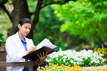 Closeup portrait, friendly, young serious confident female doctor, healthcare professional checking patient notes, bills isolated outside green trees, white flowers background. Health care reform. photo
