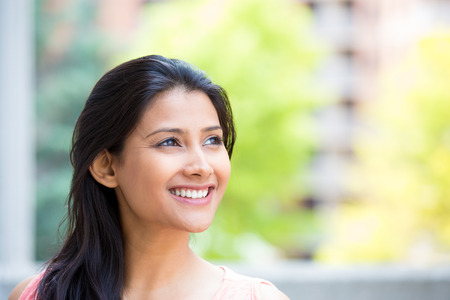 Closeup headshot portrait, smiling, joyful, happy young woman looking upwards daydreaming nice things, isolated sunny outdoors, building . Positive human emotions facial expressions feelings Stock Photo
