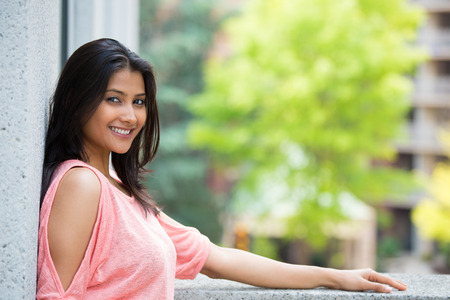 Closeup portrait, happy beautiful, smiling young woman in pink shirt, posing on outdoors balcony, isolated  with trees, and buildings, city urban life