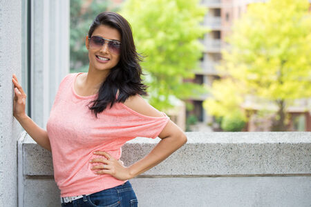 asian model: Closeup portrait, happy, gorgeous, beautiful, smiling young woman in pink shirt, sunglasses, posing on outdoors balcony, isolated with trees, and buildings, city urban life
