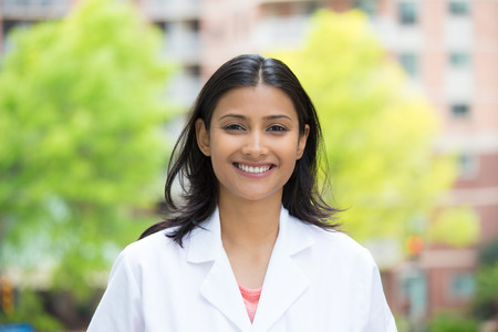 Closeup portrait of confident, smiling female health care professional in white lab coat, isolated of blurred trees and buildings