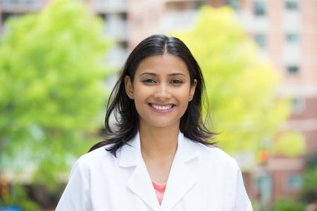 dentista: Primer retrato de una sonrisa cuidado de la salud de sexo femenino confidente profesional en bata blanca, aislado de �rboles borrosas y edificios Foto de archivo