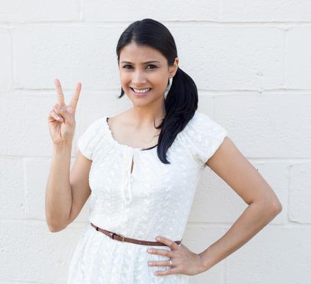 simbolo de la paz: Primer retrato, joven, feliz, sonriente, confiado, mujer emocionada dando la victoria de la paz, dos signo gesto aislado de ladrillo blanco. La emoción positiva faciales sentimientos expresión símbolos, actitud
