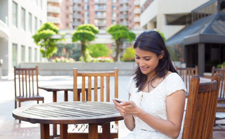 Closeup portrait, young happy business woman in white dress sitting, checking her cellphone, isolated on  a park, trees, buildings, chairs, on a sunny summer day. Business communication