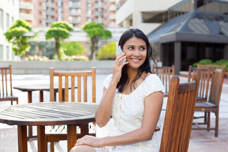 Closeup portrait, young, happy beautiful woman in white dress sitting down outside at brown table, speaking on cell phone, isolated of buildings and trees Stock Photo