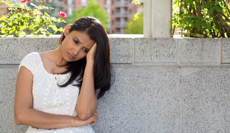 Close-up portret, doffe boos triest jonge vrouw in witte jurk zitten op de bank, echt depressief, beneden over iets, geïsoleerde grijze achtergrond. Negatieve emotie gezichtsuitdrukking gevoel lichaamstaal