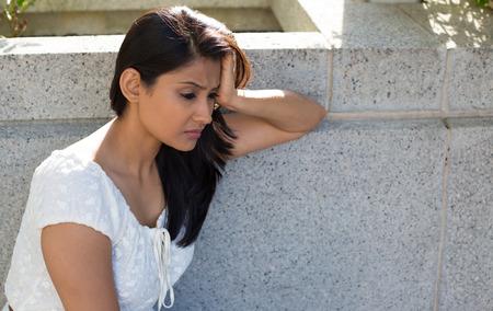 femme triste: Portrait Gros plan, terne bouleversé triste jeune femme en robe blanche assis sur un banc, vraiment déprimé, en baisse de quelque chose, isolé sur fond gris. Émotion négative expression faciale langage corporel de sentiment