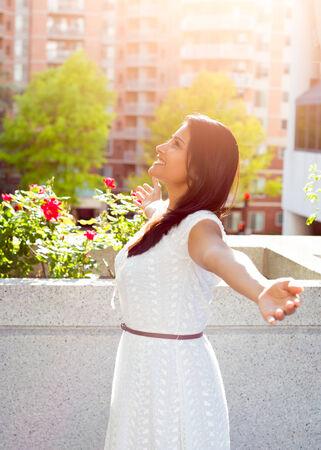 стиль жизни: Крупным планом портрет, красивая счастливая, великолепный молодая женщина, отдыхая на балконе в солнечный летний день, наслаждаясь ее выходные, город здание пейзажи и зеленые деревья. Городской образ жизни. Фото со стока