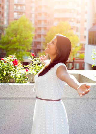 college life: Closeup portrait, beautiful happy, gorgeous young female relaxing on a balcony on a sunny summer day, enjoying her weekend,  city building scenery and green trees. Urban lifestyle. Stock Photo