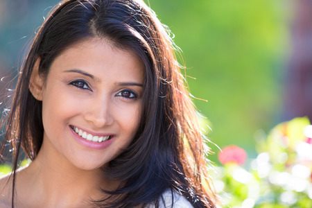 Closeup headshot portrait of confident smiling happy pretty young woman, isolated of blurred trees, flowers. Positive human emotion facial expression feelings, attitude, perception Banque d'images