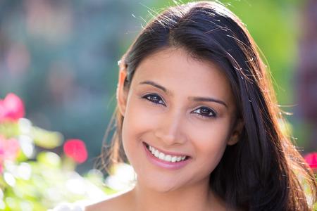 Close-up headshot portret van vertrouwen lachende gelukkige mooie jonge vrouw, geïsoleerd van wazig bomen, bloemen. Positieve menselijke emotie gezichtsuitdrukking gevoelens, houding, perceptie Stockfoto