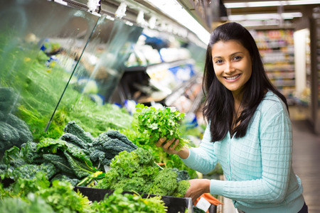 Closeup portrait, beautiful, pretty young woman in sweater picking up, choosing green leafy vegetables in grocery store Foto de archivo