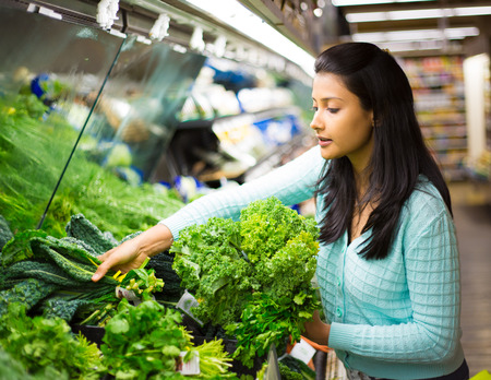 green leafy vegetables: Closeup portrait, beautiful, pretty young woman in sweater picking up, choosing green leafy vegetables in grocery store Stock Photo