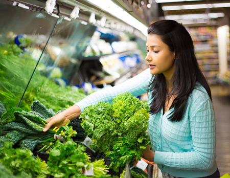 espinaca: Primer retrato, mujer hermosa, joven y bonita en suéter recogiendo, seleccionando los vegetales de hojas verdes en la tienda de comestibles