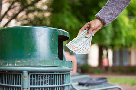 Closeup cropped portrait of someone hand tossing cash dollar bills money, hundred dollar bills in trash can, isolated outdoors green trees . Bad financial investment decisions concept